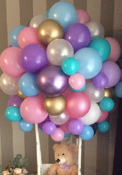 25 Balloon bouquet in mix colors tied to a basket with 6 inches teddy sitting inside