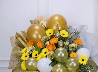 20 gerberas yellow orange with 6 gold white air balloons and leaves gold wrapping