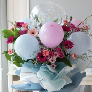 5 Air filled pink white balloons on sticks and 12 gerberas with leaves in a bouquet