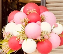 15 red white pink balloons arranged in basket with flowers