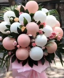 20 Blown up pink white balloons on sticks and 20 pink roses as fillers in a hand tied bouquet with pink paper wrapping