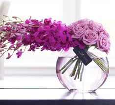 Orchids and roses arrangement in glass bowl